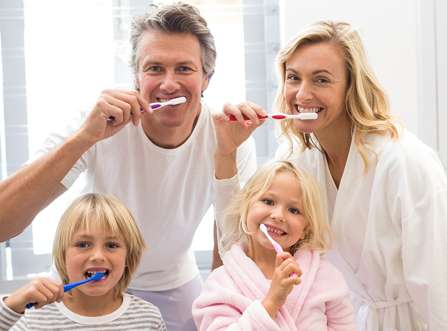 Family of 4 brushing teeth